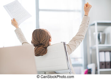 Happy business woman with document rejoicing at work. rear...