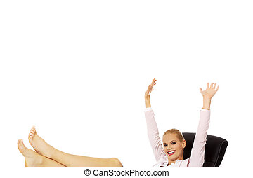 Happy business woman with hands up holding legs on the desk