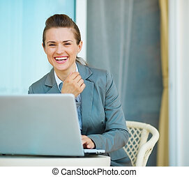 Happy business woman working on laptop
