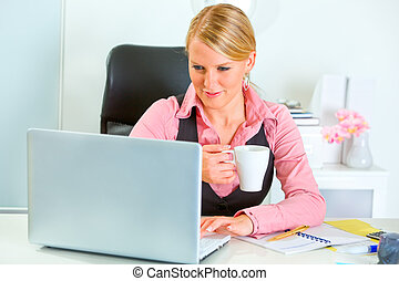 Happy business woman working on laptop and drinking coffee -...