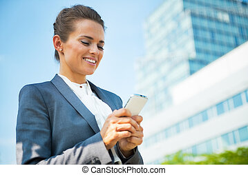 Happy business woman writing sms in front of office building