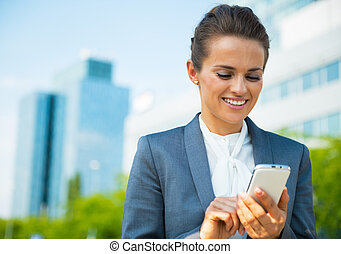 Happy business woman writing sms in office district