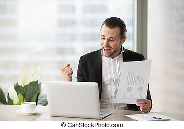 Happy businessman celebrates and screams with happiness holding