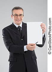 Happy businessman. Cheerful middle-aged businessman holding paper and smiling while standing isolated on grey