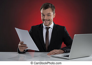 Happy businessman. Cheerful young businessman holding a paper and smiling while sitting at his working place isolated on red