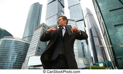 Happy businessman dances on a city street against the backdrop of a business center skyscraper