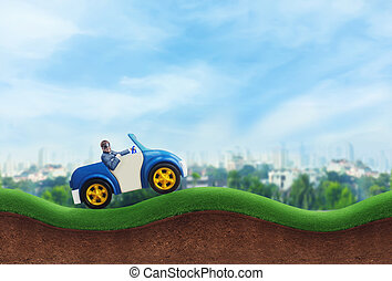 Happy businessman driving a toy car on the hills