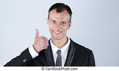 Happy businessman giving thumbs up to camera in studio