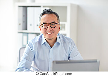 happy businessman in eyeglasses with laptop office -...