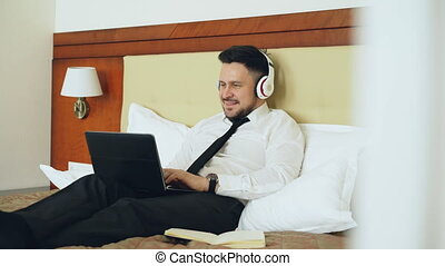 Happy businessman in headphones working at laptop computer and listening music smiling while lying in bed at hotel room. Travel, business and people concept