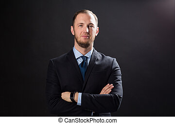 happy businessman in suit over black background