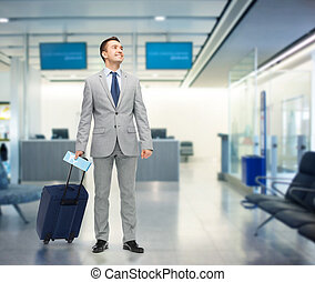 happy businessman in suit with travel bag - business trip,...