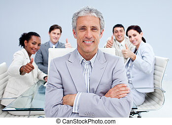 Happy businessman leading his happy team with thumbs up