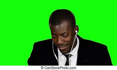 Happy businessman listening to music. Green screen