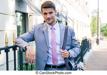 Happy businessman looking at camera outdoors
