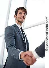 Happy businessman making handshake with businesswoman at meeting