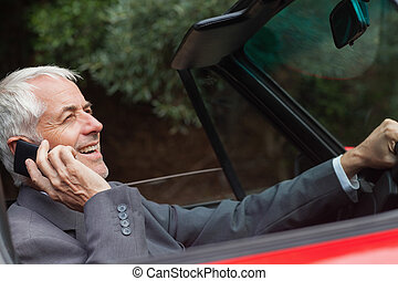 Happy businessman on the phone driving