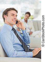 Happy businessman on the phone sitting on sofa