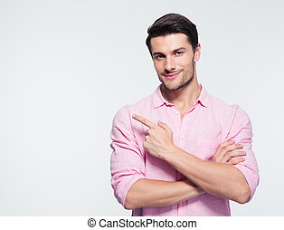 Happy businessman pointing finger away over gray background....