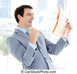 Happy businessman reading a newspaper