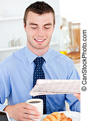 Happy businessman reading the newspaper drinking coffee