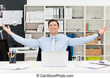 Happy businessman rejoicing in the office sitting at his...