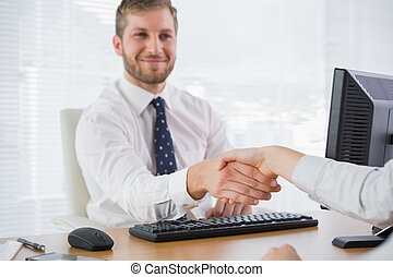 Happy businessman shaking hands with a co worker