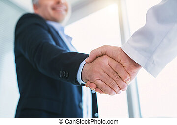 Happy businessman shaking hands with the doctor