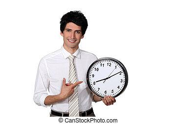 Happy businessman showing a clock