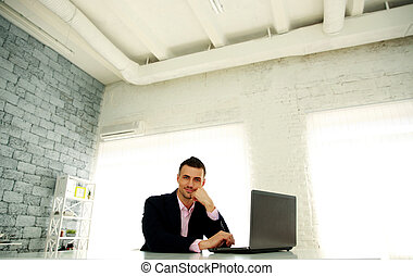 Happy businessman sitting at the table with laptop in office