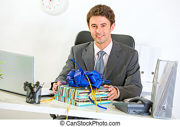 Happy businessman sitting with gift at office desk