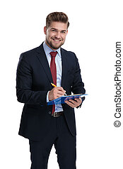 Happy businessman smiling and writing on his clipboard