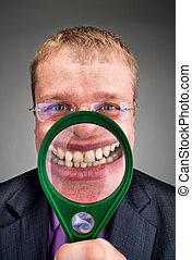 Happy businessman smiling through magnifier
