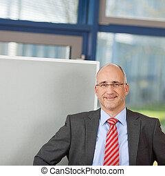 Happy Businessman Standing By Flipchart
