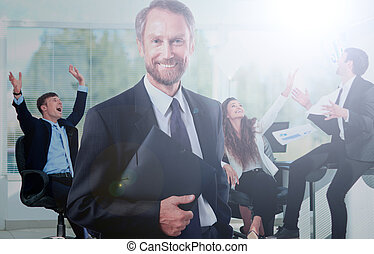 Happy businessman standing in front of his colleagues in office