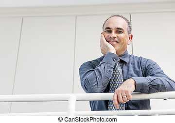 Happy businessman standing in hallway
