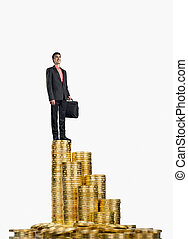 businessman standing on rouleau gold monetary - happy ...