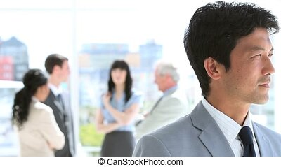 Happy businessman standing upright in front of his team