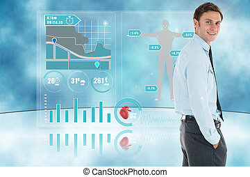 Happy businessman standing with hand in pocket against medical interface