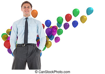 Happy businessman standing with hands in pockets against colourful balloons