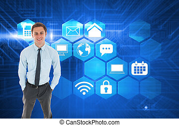 Happy businessman standing with hands in pockets against futuristic blue circuit board