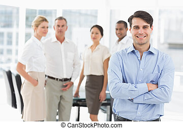 Happy businessman standing with team behind him