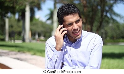 Happy businessman talking at phone.