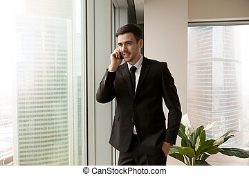 Happy businessman talking on cell standing near big office windo