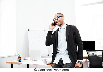Happy businessman talking on the cell phone in office