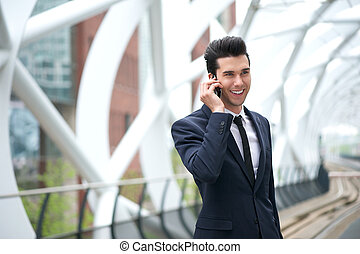 Happy businessman talking on the phone at subway station