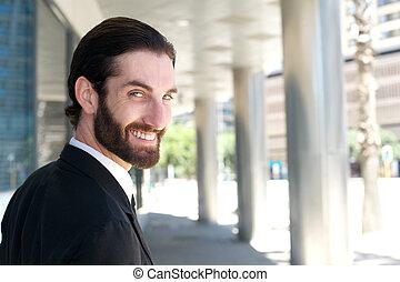 Happy businessman turning over shoulder and smiling