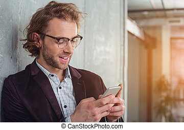 Happy businessman typing in mobile