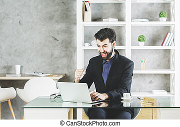 Happy businessman using laptop at workplace