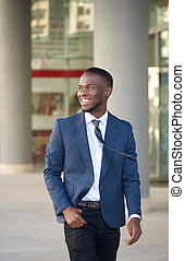 Happy businessman walking in the city
